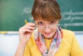 Teacher seating in front of blackboard — Stock fotografie
