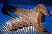 Aged Wrench over metal grid — Stockfoto