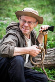 Senior tourist man with axe — Stock Photo