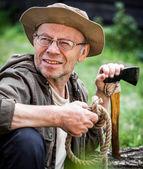 Senior tourist man with axe — Stock Photo