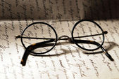 Old glasses on a letter — Stock Photo