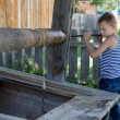 Boy picks up a bucket with water — Stock Photo #20694617