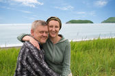 Happy middle aged couple by the sea. — Stock Photo