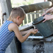 Boy washes well water. — Stock Photo