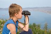 Boy looking through binoculars of the mountain. — Stock Photo