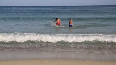 Senior and junior brothers swimming in sea. — Stock Video