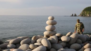 Hiker creates ballast of oval stones on the beach. — Stock Video