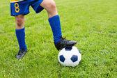 Bola de futebol com seu pés de menino — Foto Stock