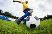 少年サッカー選手がボールを打つ — ストック写真