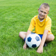 Boy football player with the ball is sitting on the football fie — Stock Photo