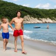 Senior and junior brothers walk along the beach. — Stock Photo