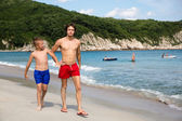 Senior ve junior kardeşler sahilde yürümek. — Stok fotoğraf
