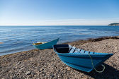 Wooden fishing boats on the sea pebble beach — Stock Photo
