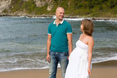 Pregnant woman and her husband by the sea. — Stock Photo