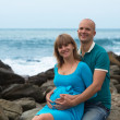 Happy pregnant woman and her husband on the coast. — Стоковая фотография