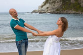 Happy pregnant woman and her husband strolling by sea. — Stock Photo