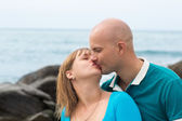 Happy pregnant woman and her husband kissing by the sea. — Stock Photo