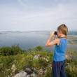 Boy looking through binoculars from the top of the mountain to t — Stock Photo #33011715