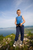 Boy hiker with binoculars on top of a mountain. — Stockfoto