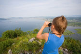 Boy looking through binoculars from the top of the mountain — Stok fotoğraf