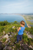Boy hiker looking down from the top of the mountain. — Stock Photo