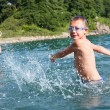 Boy creates large splashes in the sea. — Stock Photo