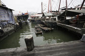 Fishing boats are at the wooden pier in the port of Macau. — Stock Photo