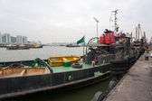 Tugboat and fishing vessels are at berth in the port of Macao. — Stock Photo