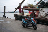 Moped and fishing boat in the fishing port in Macau. — Stock Photo
