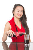 Cheerful Asian girl pours a Coca-Cola into a glass — Stock Photo