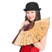 Cheerful girl asian in black hat with a fan — Stok fotoğraf