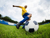 Boy soccer player hits the football ball  — Stock Photo