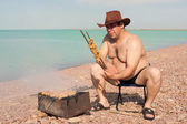 Adult man prepares fried meat. On the lake. Rest. — Stock Photo