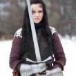 Beautiful young woman in medieval clothes holding a sword — Stock Photo #21461731