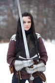 Beautiful young woman in medieval clothes holding a sword — Stock Photo