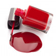 Red nail polish bottle with spilled varnish isolated on white ba — Stock Photo