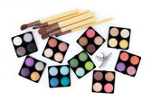 Various eyeshadow palettes, fake eyelashes and cosmetic brushes, — Stock Photo
