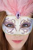 Beautiful teenage girl wearing carnival mask with pink feathers — Stock Photo