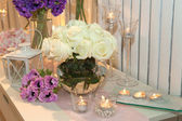 Table decorated with candles and white roses — Stock fotografie