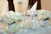 Table decorated with candles and white roses — Photo