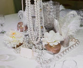 Table decorated with feathers, pearls and candles — Stockfoto