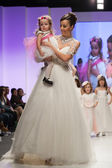 Fashion model in wedding dress with child model dressed as little bridesmaid — Stock Photo