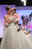 Fashion model in wedding dress with child model dressed as little bridesmaid — Stockfoto