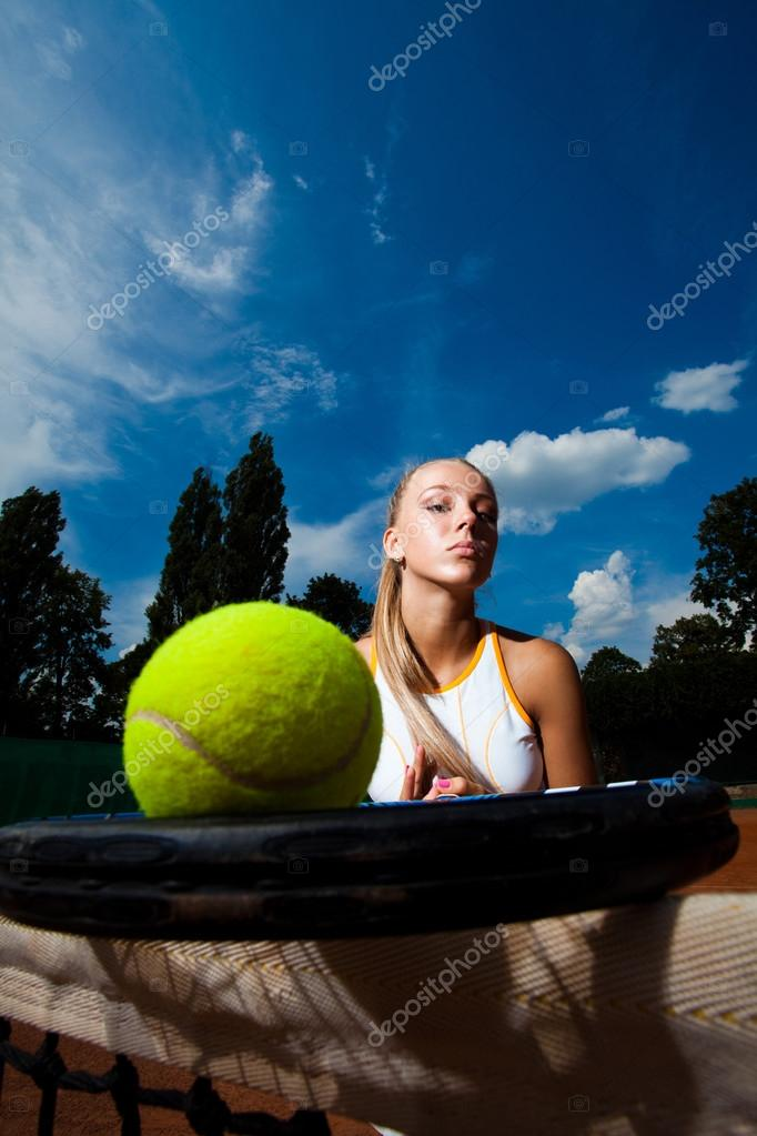 Tennis ball on the racket to the background of young woman. Close-up  Stock Photo #14342121