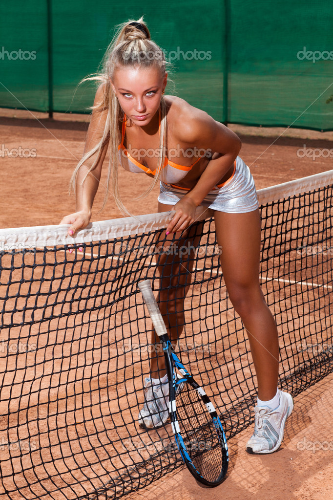 Sporty woman in bra and short skirt trying to get over a tennis net — Stock Photo #14342205