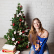 Modern girl near christmas tree — Stock Photo #37289387