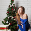 Modern girl near christmas tree — Stock Photo