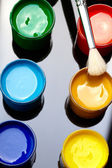 Paint buckets with paintbrush over dark background — Stock Photo