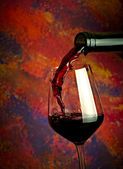 Red wine pouring in glass over grange background — Stock Photo
