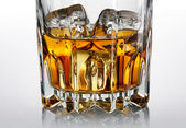 Glass of whiskey and ice over dark background — Stock Photo